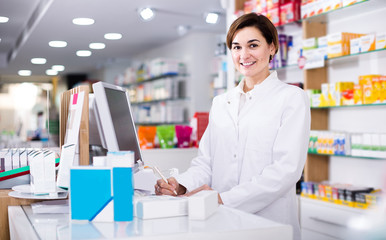 Photo sur Plexiglas Pharmacie female pharmacist checking assortment of drugs in pharmacy
