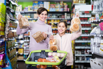 positive woman with daughter choosing bread in supermarket