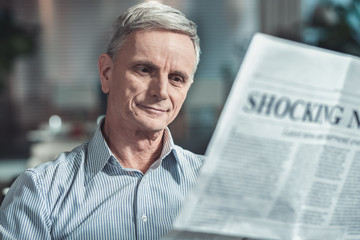 Do not bother me. Handsome mature male being deep in thoughts while reading morning news