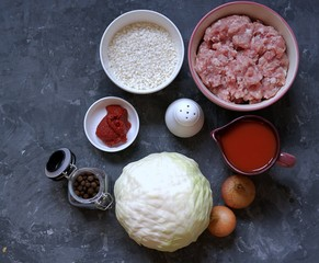 Ingredients for cooking cabbage rolls with minced meat and rice. Cabbage, minced meat, tomato juice, onion, rice, tomato paste, salt, spices.