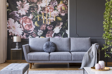 Blanket on grey couch in living room interior with flowers wallpaper and lamp on table. Real photo Wall mural