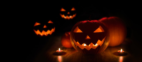 halloween and holidays concept - many spooky carved pumpkin jack-o-lanterns with candles in darkness