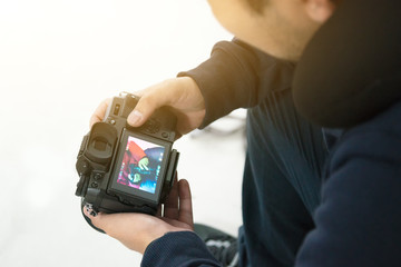 man check and review photo in camera during travel trip
