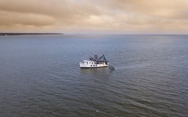 Aerial view of shrimp boat off the coast of South Carolina, USA at sunrise.