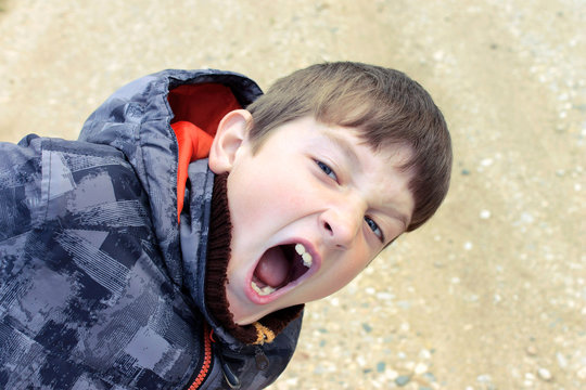 A shouting, screaming boy with wide open mouth