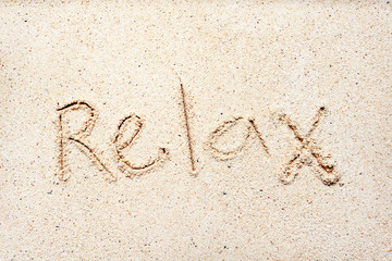 "Handwriting words ""relax"" on sand"