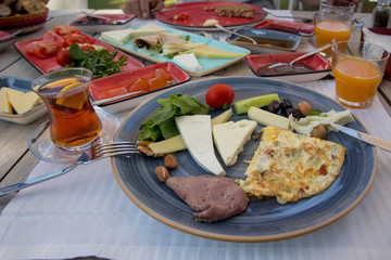 breakfast prepared on wooden table, cheeses, jams, tomatoes, cucumber, smoked meat, butter, honey, olives, breads