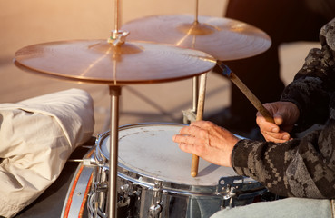Old man playing drums on street