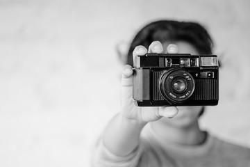 Persona joven sosteniendo una cámara vieja