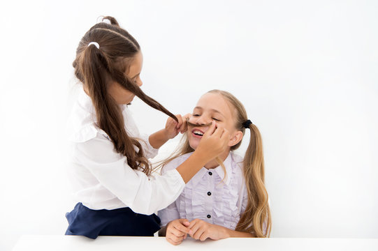 Girls make mustache with long hair. Lets imagine you were boy. Girl cheerful playful mood play with hair as mustache. Masculinity and femininity concept. Hairstyle fashion. Schoolgirls tidy uniforms