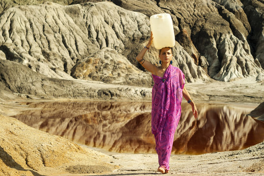 girl of oriental appearance in a sari carries on her head a large plastic canister  with water over a desert area
