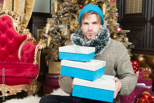 59a2aa48ddb6a Guy with gift boxes sit at Christmas tree