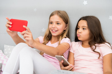 Kids taking selfie in bedroom. Pajamas party concept. Girlish leisure happy childhood. Girls long hair with smartphones use modern technology. Lets take selfie. Send photo your friends social network
