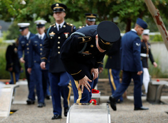A member of the U.S. Army checks the name on a memorial bench during the 17th annual September 11 observance ceremony at the Pentagon in Washington