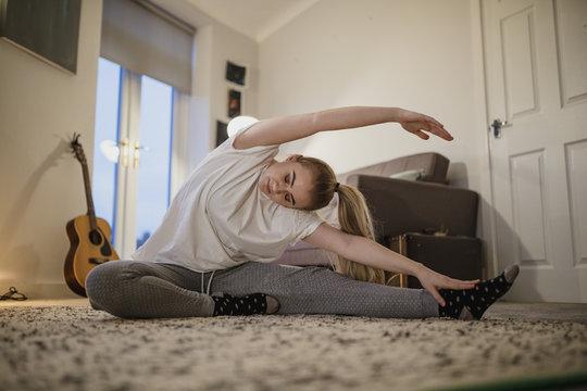 University student is doing yoga in her living room.