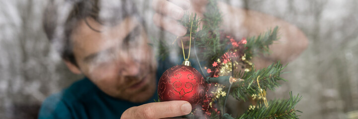 Young man hanging red Christmas decoration on a tree