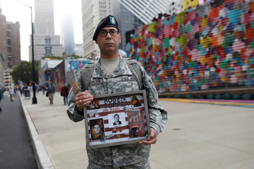 U.S. Army Reserve Sgt. Edwin holds a photo of his cousin Ruben Correa before entering ceremonies marking the 17th anniversary of the September 11, 2001 attacks on the World Trade Center in New York
