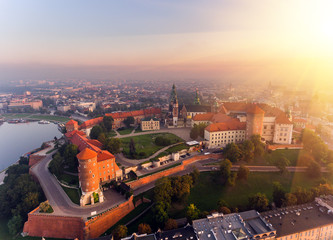 Aerial view Royal Wawel Castle and Gothic Cathedral in Cracow, Poland, with Renaissance Sigismund Chapel with golden dome, fortified walls, yard, park and tourists.