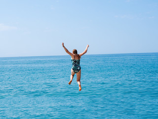 Young woman jumping into the sea