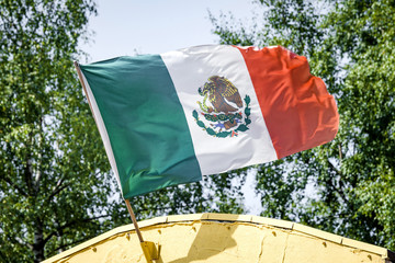 Mexican flag on a yellow building waving