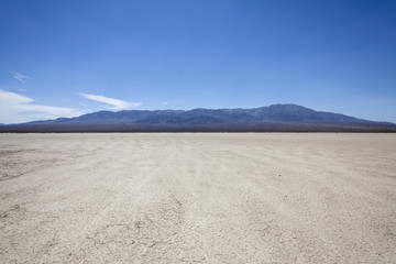 In de dag Droogte Mojave desert dry lake with mountain backdrop near Death Valley in California.