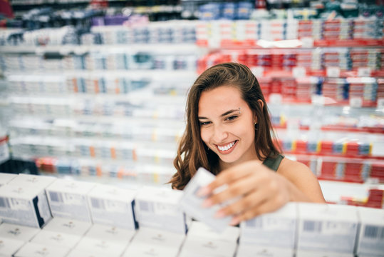 Young woman holding cosmetics in her hand in drugstore department of a supermarket.
