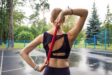 Beautiful girl in sports top and leggings trains with red elastic rope on sports grounds in the park.Training in the rain