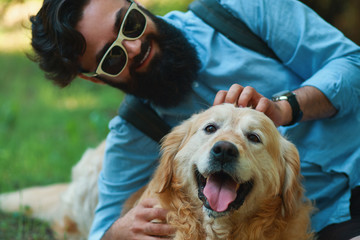 Man with beard and his small yellow dog playing and enjoying sun