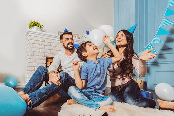 Kids birthday. Vigorous merry family laughing while playing with balloons