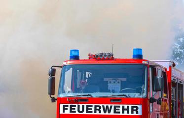 Feuerwehr Fahrzeug  mit Blaulicht steht vor einer Rauchwolke