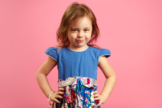 Horizontal isolated shot of four year old girl in beautiful blue dress on pink background.