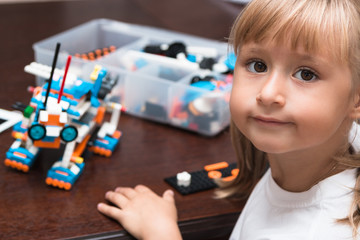 Cute little girl is playing with robot at home and programming it on tablet. STEM education.