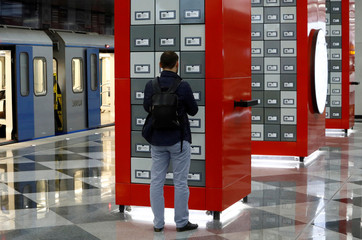 A passenger scans a QR code with his mobile phone to download an e-book at Rasskazovka metro station in Moscow