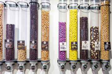 Front view of variety of chocolate candy dispensers in a candy store