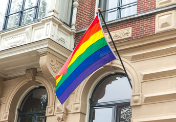 The rainbow pride LGBT flag blows in the wind on a building in Amsterdam