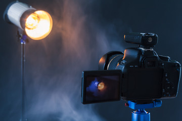 Photo of the camera on a blue tripod that photographs in the studio a professional lighting device in the smoke. Studio lights and smoke equipment. Advertising photo session of the lighting device