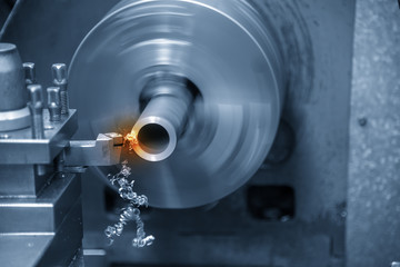 The  operation of lathe machine cutting the steel shaft in the light blue scene with lighting effect.