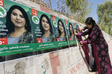 A candidate puts her campaign poster ahead of regional elections, in Sulaimaniya