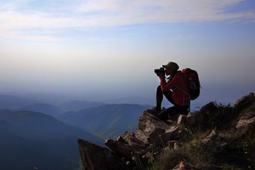 Female tourist taking photo on mountain peak