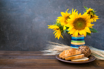 Autumn harvest, natural products, Greeting card concept. Still life with beautiful sunflowers in vase, sliced white bread on clay plate, wheat spikelets on wooden rustic background.