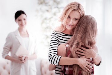 Calm mother. Cheerful kind professional psychologist smiling and feeling pleased while looking at the loving mother hugging her pretty teenage daughter