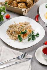 Boilden barley groats with chicken sausage served with parsley twig on white plate