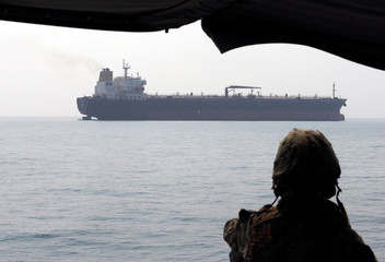 A U.S. Navy soldier onboard Mark VI Patrol Boat stands guard as a tanker makes its way towards Bahrain port, during an exercise of U.S./UK Mine Countermeasures (MCMEX) taking place in Arabian Sea