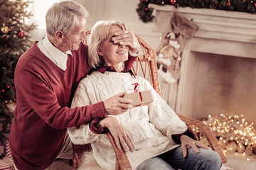 Dont look. Caring senior smiling man staying on the knee behind his wife who sitting on the chair holding a present and closing womans eyes.