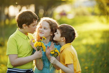 Little boys give his girl friend bouqet of yellow dandelions, springtime outdoors background.