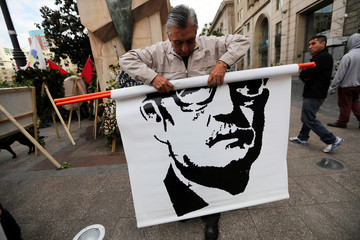 A man rolls up an image of Chile's late President Salvador Allende during a rally marking the 45th anniversary of the 1973 Chile military coup, in Santiago
