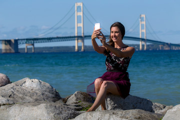 Traveller on road trip vacation taking scenic selfie picture by marina blue ocean water