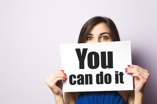 Woman holding white paper with text You can do it, Concept of motivation