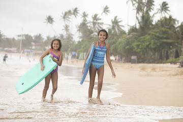 Two beautiful young mixed race sister girls walking on the beach wearing swim wear laughing with boogie boards