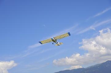 Aereo ultraleggero in volo dopo il decollo con cielo azzurro e nuvole bianche